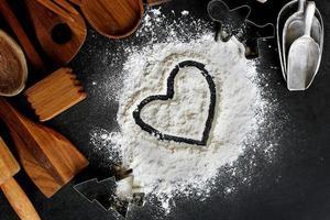cuore disegnato nella farina da forno con bordo di forniture da cucina foto
