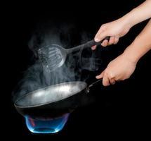 chef di cucina con fiamma in una padella antiaderente