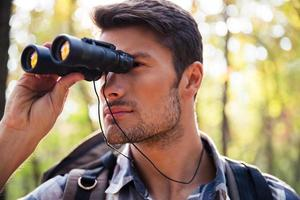 uomo che guarda attraverso il binocolo nella foresta