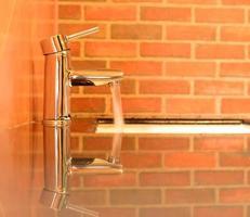 rubinetto in metallo con acqua corrente
