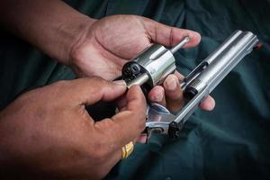 mano che tiene la pistola mostra il cilindro di stoccaggio foto