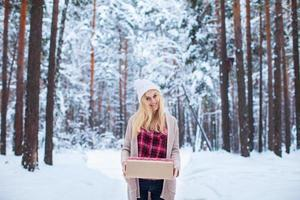 ragazza che tiene un regalo di Natale nella foresta di inverno