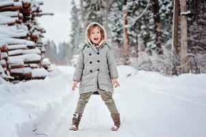bambina sulla passeggiata invernale nel bosco innevato