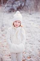 ragazza carina bambino che cammina nella foresta ghiacciata di inverno