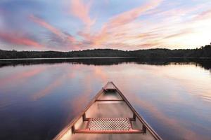 prua di canoa su un lago al tramonto foto