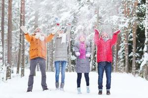 gruppo di amici felici che giocano con la neve nella foresta