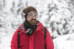 giovane uomo con occhiali da neve sorride nella fotocamera foto