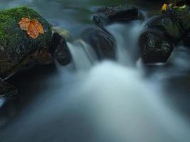 masso di basalto scivoloso nel ruscello rapido di montagna sfocata. foto