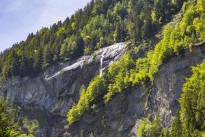 Alpi svizzere viste attraverso la foresta nel parco naturale di Blausee foto