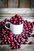 mirtilli rossi su una tazza su fondo di legno rustico foto