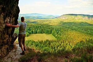 alto turista che si arrampica su una scogliera appuntita e si affaccia su una splendida vista