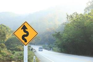 segno curva acuta accanto alla strada di montagna