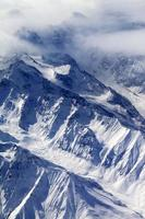 vista dall'alto sulle montagne innevate e sul ghiacciaio nella nebbia