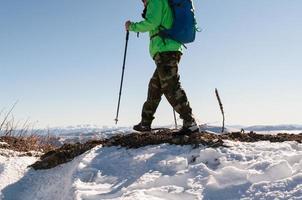 zaino in spalla che cammina sul picco di montagna foto