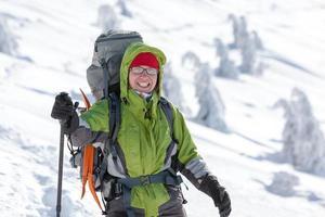 escursionista che propone alla macchina fotografica in montagna invernale foto