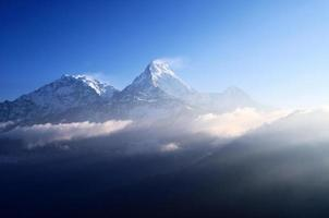 raggi del sole sulla montagna innevata machapuchare, annapurna himalaya foto