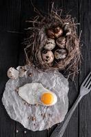uova di quaglia nel nido e un uovo fritto foto