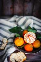 mandarini con foglie su fondo di legno rustico