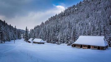 vecchi cottage in legno in montagna invernale foto