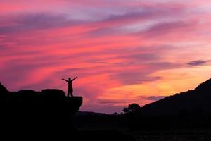 sagoma di un uomo sulla roccia al tramonto foto