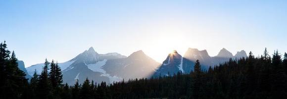 sole che tramonta dietro le cime delle montagne foto