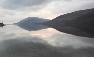 riflessioni di montagna su un lago in Scozia foto