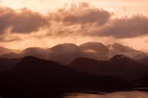 silhouette di montagne sopra l'acqua sotto le nuvole arancioni Cloudscape foto