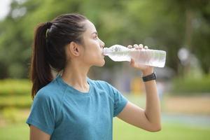 donna acqua potabile dopo l'allenamento in un parco