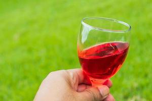 vicino la mano che tiene il vino rosso