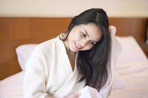 sorridente giovane donna in camera da letto