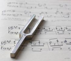 forcone di accordatura in metallo sopra fogli musicali foto