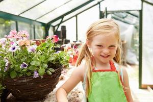 ragazza che coltiva piante in serra foto