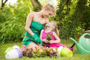 bella madre e figlia che piantano fiori foto