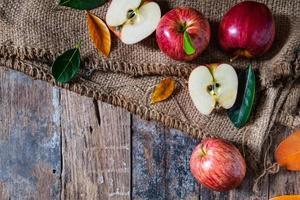 mele rosse su un vecchio tavolo di legno