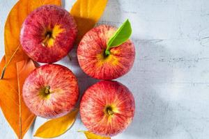 mele rosse su un tavolo di legno bianco
