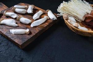 funghi freschi su legno e in una ciotola foto