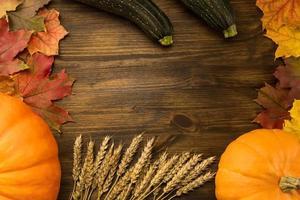 zucca gialla matura, foglie di acero, mele rosse, fondo in legno di grano.