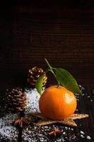 mandarino su assi di legno con neve e cono di abete