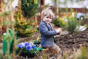 ragazzino che fa il giardinaggio e che pianta i fiori in giardino