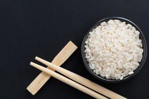 riso e bacchette per sushi su sfondo nero, vista dall'alto