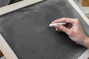 le giovani donne scrivono sulla lavagna sporca in bianco foto