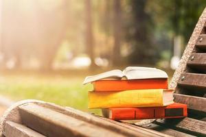 pila di libri con copertina rigida, libro aperto sdraiato su una panchina