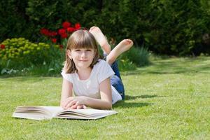 ragazza che legge un libro in un giardino foto