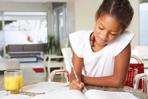 giovane ragazza felice di fare i compiti in cucina