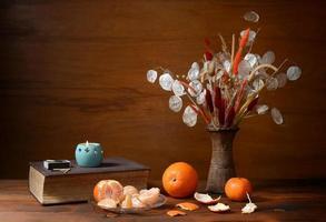arance fresche e fiori secchi in un vaso