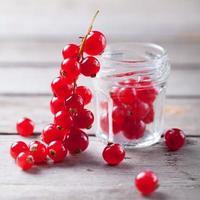 ribes rosso su un ramo vicino a un barattolo di vetro