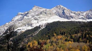 montagna dalle vette innevate con alberi d'autunno