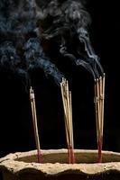 bastoncini di incenso con fumo su sfondo nero