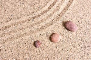 giardino zen onde di sabbia e sculture di roccia foto