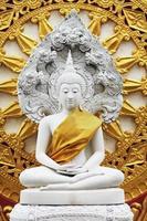 statua di buddha bianca e dorata scolpita nella pietra. foto